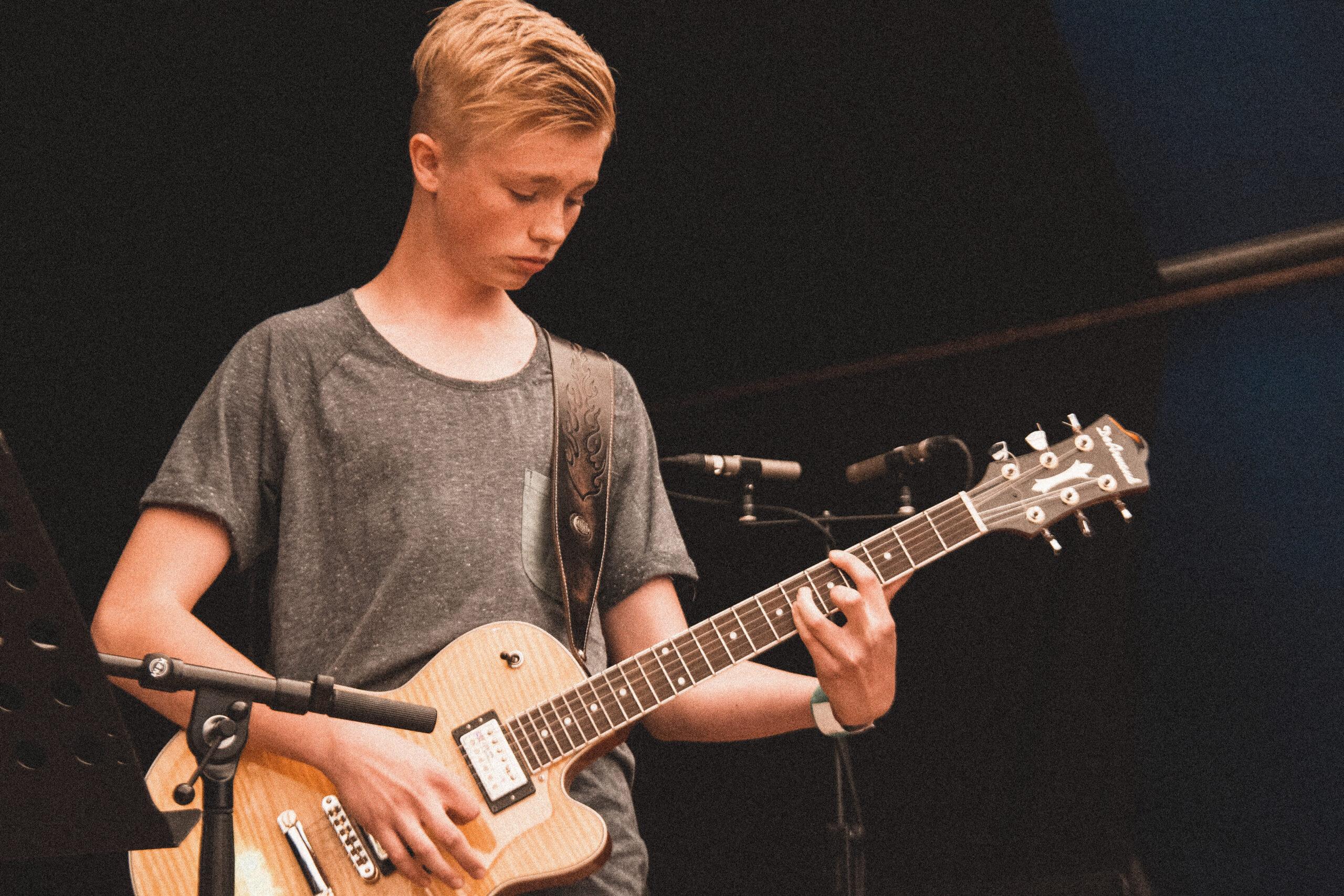 dreng der spiller på guitar